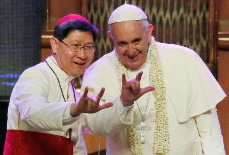 """Filipino Cardinal Luis Antonio Tagle, left, shows Pope Francis how to give the popular hand sign for """"I love you"""" at the Mall of Asia arena in Manila, Philippines, Friday, Jan. 16, 2015. Pope Francis is on a five-day apostolic visit in this predominantly Catholic nation in Asia. (AP Photo/Wally Santana)"""