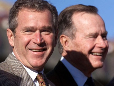 Texas Gov. George W. Bush, left, and his father, former President George Bush, watch ceremonies before the start of a football game on Nov. 26, 1999 in College Station, Texas. (AP Photo/David J. Phillip)
